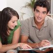Stock Photo: Young couple at home skimming through catalogue