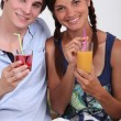 Two teenagers with fruit juice - Stock Photo