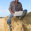 图库照片: Farmer seated on straw bale and doing computer