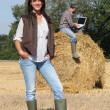 Attractive lady farmer standing in front of her husband on a haystack using — Stock Photo #8110602