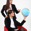 Duo of businesswomen with globe — Stock Photo #8110841
