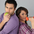 Young man with an apple and woman with a dumbbell — Stock Photo
