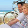 Profile picture of couple sat next to bicycles at the beach — Stock Photo #8111356
