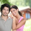 Couple standing in front of a holiday cabin — Stock Photo #8111379