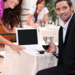 Couple looking at a blank computer screen in a restaurant — Stock Photo