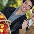 Young couple all smiles with basket full of apples — Stock Photo #8111480