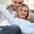 Couple lounging comfortably on a sofa — Stock Photo #8111524