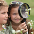 Two little girls with magnifying glasses — Stock Photo