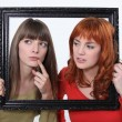 Girls behind a wooden frame - Stockfoto