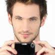 Young man with a digital camera — Stock Photo