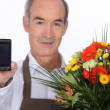 A florist showing a cell phone — Stock Photo