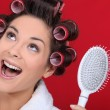 Excited brunette wearing hair-rollers — Stock Photo #8111956