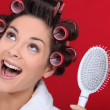 Stock Photo: Excited brunette wearing hair-rollers