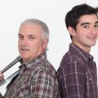 Craftsman and apprentice standing back to back - Stock Photo