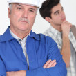 A construction worker and his trainee. — Stock Photo