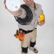 An electrician holding a fire alarm. — Stock Photo