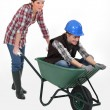 Stock Photo: Two craftswomen having fun with a wheelbarrow