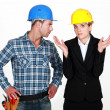 Female architect being assertive with craftsman — Stock Photo