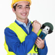 Tradesman holding an angle grinder — Stock Photo