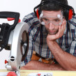 A man staring at a circular saw. - Stock Photo