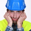 A grumpy and frustrated tradesman - Stock Photo