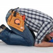 Construction worker curled up on the floor - Stock Photo