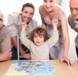 Family gathered around jigsaw puzzle — Stock Photo