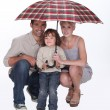 Young family crouching under an umbrella — Stock Photo #8114817