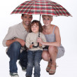 Young family crouching under an umbrella - Stock Photo