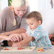 Little boy and young woman playing to puzzle — Stock Photo #8114956