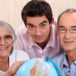 Grown-up family looking at globe — Foto Stock #8115042