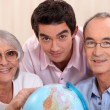 Foto Stock: Grown-up family looking at globe