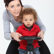 A mother and her son playing with a steering wheel — Stock Photo #8115162