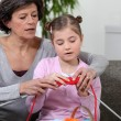 Grandmother teaching granddaughter how to knit — Stock Photo