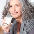 Stock Photo: Woman drinking a glass of milk
