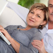 Stock Photo: Middle-aged couple looking at their laptop