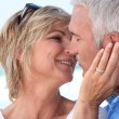 Middle aged couple kissing at the beach. — Stock Photo