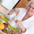 Elderly woman having breakfast - Stock Photo