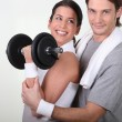 Couple working out with weights — Stockfoto