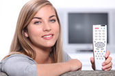 Blond woman at home holding TV remote control — Stock Photo