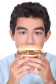 Young man facing a hamburger — Stock Photo