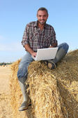 Farmer seated on straw bale and doing computer — Стоковое фото