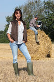 Attractive lady farmer standing in front of her husband on a haystack using — Stock Photo