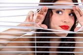 Woman peering through some blinds — Stock Photo