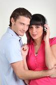 Brunette with earphones and boyfriend cuddling — Stock Photo