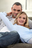 Couple lounging comfortably on a sofa — Stock Photo