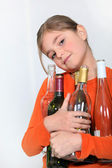 Young girl holding empty wine bottles — Stock Photo