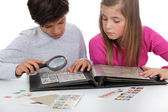 Kids watching a stamps album — Stock Photo