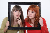 Girls behind a wooden frame — Stock Photo