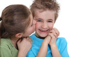 Playful little boy being kissed by a little girl — Stock Photo